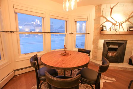 Game table in living area with gas fireplace, views of Main Street