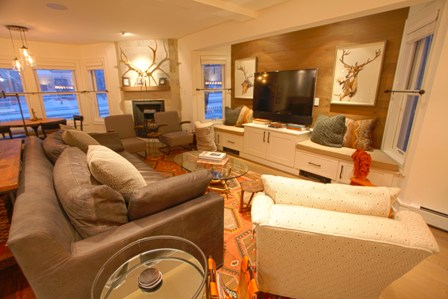 Spacious, open living area with large leather sofa, club chairs, flat-screen TV
